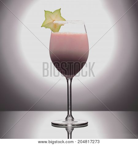 Milk Cocktail In Wineglass Decorated With Green Carambola On Studio Background.