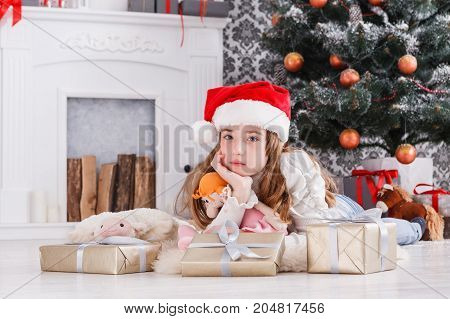 Beautiful pensive girl unwrap christmas present box on holiday morning in beautiful room interior. Female child open Xmas gift near decorated fir tree and fireplace. Winter holidays concept