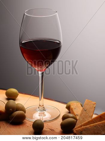Wineglasses With Red Wine On Wood With Cheese And Green Olives. Studio Background