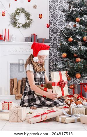 Beautiful happy girl in santa hat unwrap christmas present box on holiday morning in beautiful room interior. Female child open Xmas gift near decorated fir tree and fireplace. Winter holidays concept