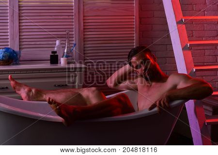 Macho Sitting Naked In Bathtub With Erotic Atmosphere Around