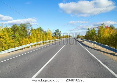 Autumn bright landscape. Road through forest with blue sky and clouds