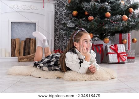 Beautiful happy girl portrait with christmas present box on holiday morning in beautiful room interior. Female child got Xmas gift near decorated fir tree and fireplace. Winter holidays concept