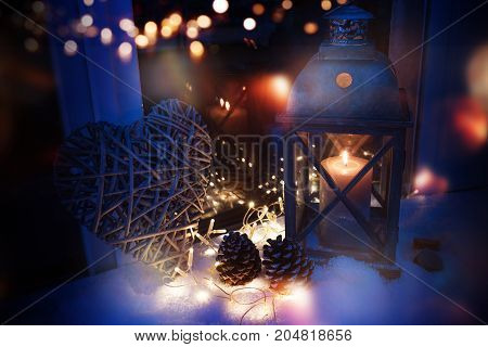 Winter decoration in snow with a lantern in luminous blue light and golden bokeh