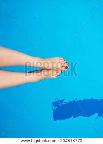 Woman's feet with red nails on the swimming pool