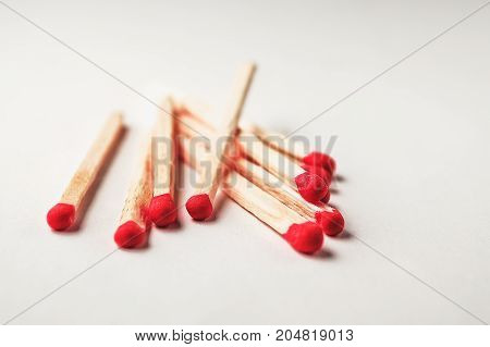 Matches on a white background with pink heads scattered