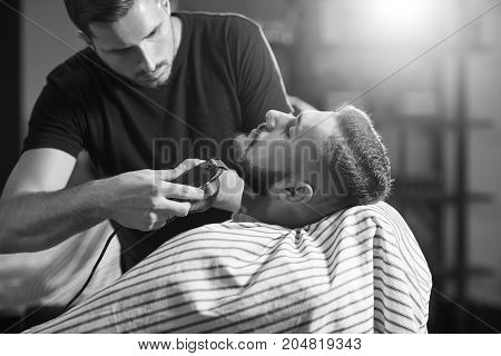 Monochrome shot of a bearded young man at the barbershop getting his beard shaped and trimmed.