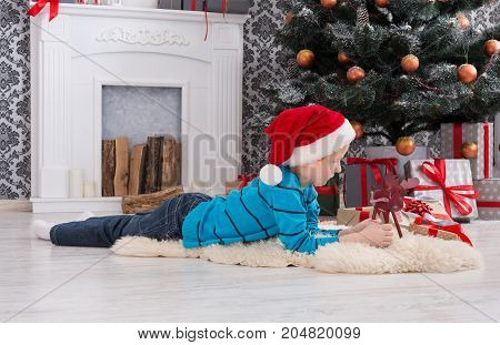 Cute boy in santa hat playing with toy deer. Christmas present on holiday morning in beautiful room. Male child got Xmas gift, lying near decorated fir tree and fireplace. Winter holidays concept