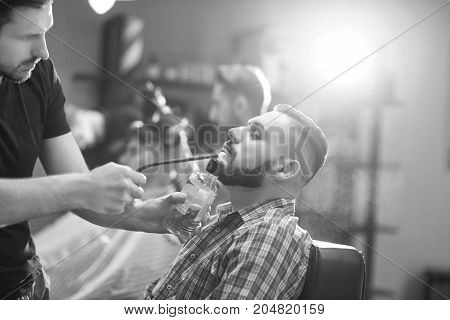 Monochrome shot of a handsome bearded man being sprayed with cologne at the local barbershop.