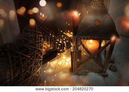 Winter decoration at evening with a burning lantern in the snow and golden bokeh for christmas