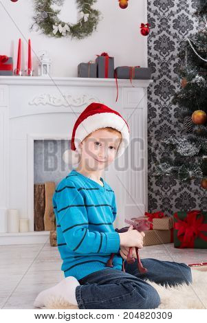 Cute happy boy in santa hat holding toy. Christmas present on holiday morning in beautiful room. Child got Xmas gift near decorated fir tree and fireplace posing on camera. Winter holidays concept