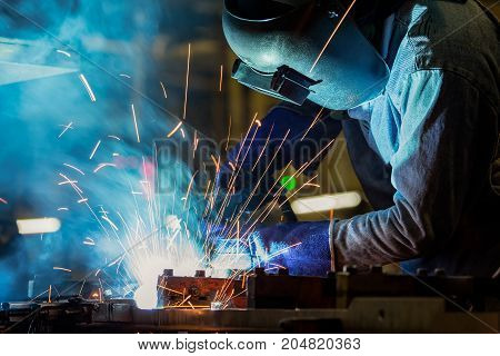 Industrial worker with protective mask is welding metal in car factory