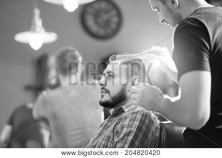 Monochrome shot of a professional barber styling hair of a young handsome man.