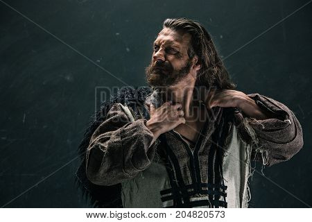 Actor in makeup, a poor man on black studio background. The bum in canvas rags. concept of vagrancy and survival. concept of pain and suffering poster