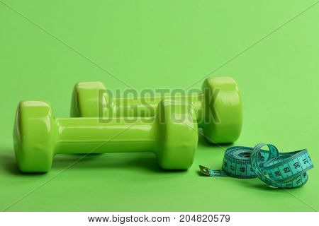 Dumbbells In Bright Green Color On Green Background