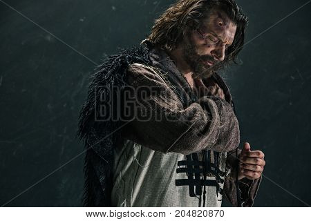 Actor in makeup, a poor man on black studio background. The bum in canvas rags. concept of vagrancy and survival. concept of pain and suffering