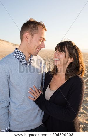 Loving Young Couple Walk On The Beach In Autumn