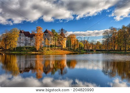 An ancient castle with towers on an island by the lake among autumn yellow trees with reflection in the water. Jaunpils