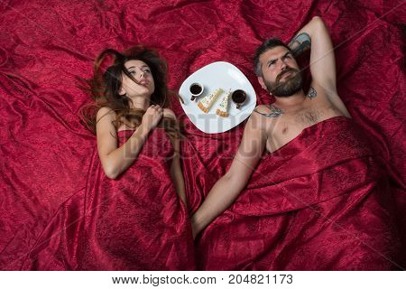 Couple In Love Lies On Burgundy Sheets, Holding Hands