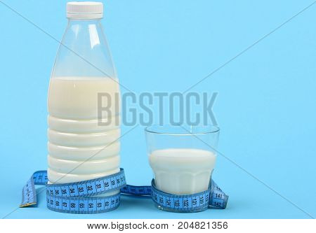 Bottle And Glass Of Milk With Blue Measuring Tape