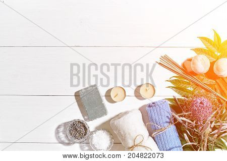 Spa products. Bath salts, dry flowers lavender, soap, candles and towel. Aroma sticks, aromatherapy. Flat lay on white wooden background, top view. Still life. Close-up. Copy space. Sun flare