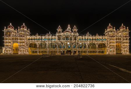 Mysore India - October 27 2013: Wide frontal shot of entire East facade of Mysore Palace at Sound and Light show. Beige building with towers and maroon domes. Central tower with golden domes.