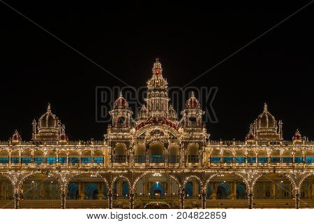 Mysore India - October 27 2013: Upper level with towers and domes of facade center of Mysore Palace at nightly Sound and Light show. Beige building with towers and maroon domes. Hundreds of lights.