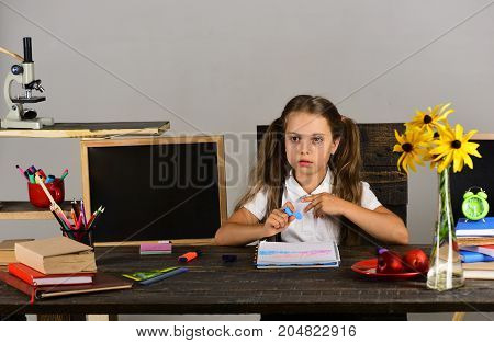 Schoolgirl with serious face writes in notebook in her classroom. Kid and school supplies on grey wall background. Girl sits at desk with colorful stationery books and flowers. Back to school concept