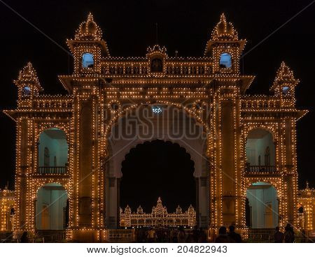 Mysore India - October 27 2013: Main East gate of Mysore Palace illuminated at nightly Sound and Light show. Palace self visible through gate. Hundreds of lights. Seen from outside domain.