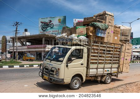 Mysore India - October 28 2013: Beige extremely overloaded parked delivery van along Hunsur Road under blue sky. Street scene with billboards and business buildings.