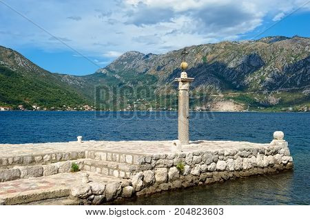 MONTENEGRO, PERAST - AUGUST 13, 2017: Stone pillar on the artificial island of Our Lady of the Rocks stands on the site where the icon of Our Lady was found
