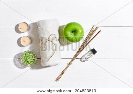 Spa products. Bath salts, soap, candles and towel. Aroma sticks, aromatherapy. Flat lay on white wooden background, top view. Still life. Close-up. Copy space