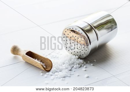 salt crystals with metal salt shaker on wooden table
