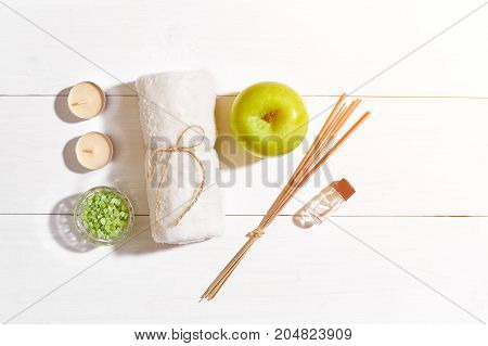 Spa products. Bath salts, soap, candles and towel. Aroma sticks, aromatherapy. Flat lay on white wooden background, top view. Still life. Close-up. Copy space. Sun flare