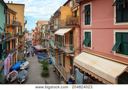 View of a Manarola Road. Small motor boats in winter are paved in the street under the houses. Manarola is a small town in the province of La Spezia in Liguria northern Italy.