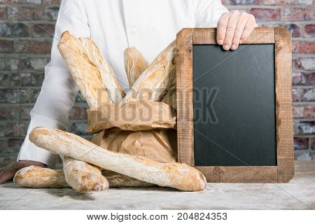 a baker holding bread french baguettes with chalkboard