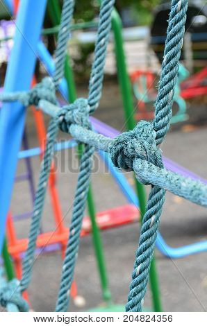 Close up image of weathered knot rope climbing net at children playground as a symbol of trust teamwork and collaboration