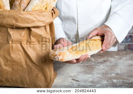 a baker holding traditional bread french baguettes