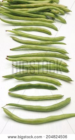 String bean raw food isolate on wood white sort spacing and macro photo focus at center around are blur.