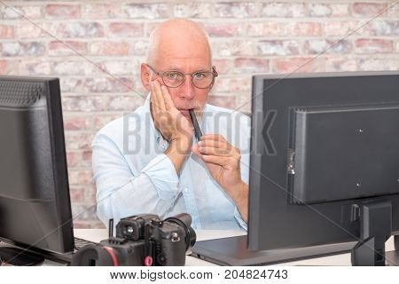 a mature businessman with glasses using computer