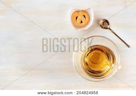 An overhead photo of a cup of tea on a light background, with a vintage spoon with caramelized sugar, a Danish butter cookie, and a place for text