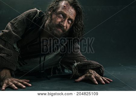 Actor in makeup, a poor man on black studio background. The bum in canvas rags. Concept of vagrancy and survival. Concept of pain and suffering. The wounded man crawling to salvation poster