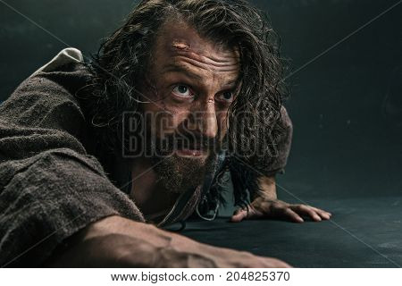 Actor in makeup, a poor man on black studio background. The bum in canvas rags. Concept of vagrancy and survival. Concept of pain and suffering. The wounded man crawling to salvation