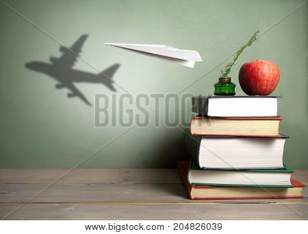 Paper plane with shadow of an aircraft next to a stack of books quill and apple
