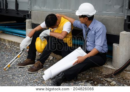 Sad Asian unemployed young foreman cry while Senior engineer manager comfort and cheer up at construction site. bad economy situation forces to layoff employees.