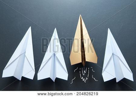 Gold paper plane standing out in a line