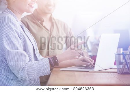 Lady in striped jacket pointing at laptop screen with her finger