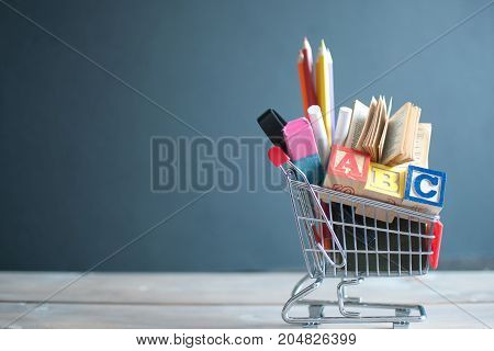 Shopping cart filled with stationery against a chalkboard