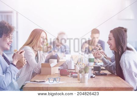 Beautiful young women having lunch break at an advert agency office