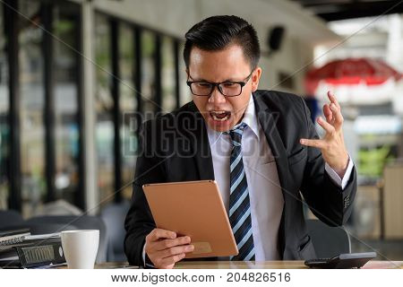 Angry Businessman See Bad News By Tablet